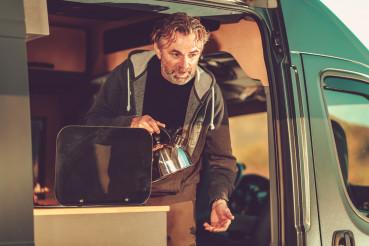 Men with Water Kettle Inside Camper Van