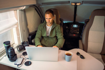 Men Working Remotely From Camper Van Using Internet Connection