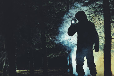Mysterious Men with Flashlight in His Hand In Dark Foggy Forest
