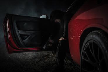 Pensive Caucasian Gangster with Handgun Inside His Car
