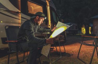 Planning Next Day Trip in Front of His Camper Van