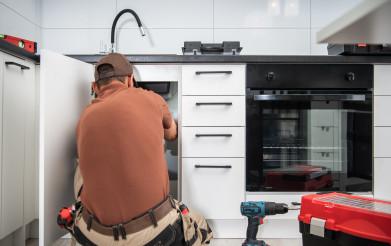 Plumbing Technician Finishing Kitchen Sink Pipeline Installation