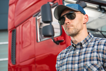 Portrait of Caucasian Truck Driver in Front of His Vehicle