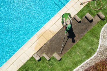 Pro Landscaper Installing Brand New Grass Turfs Around Pool