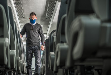 Public Transportation Passenger in Face Mask Walking Along Coach Bus Alley