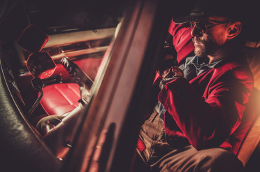 Red Suit and Cowboy Hat Wearing Men Inside Classic Car
