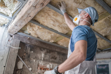 Replacing Old Attic Mineral Wool Insulation by Worker