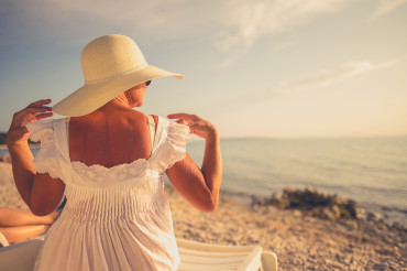 Retired Woman in Sun Protection Hat Relaxing on a Beach