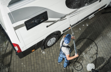 RV Service Worker Pressure Washing Camper Van