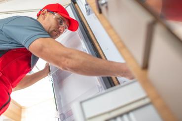 RV Technician Looking Inside Camper Refrigerator