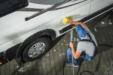 RV Camper Owner Washing Vehicle.
