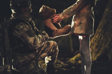 Soldier Giving Teddy Bear Toy to Caucasian Girl