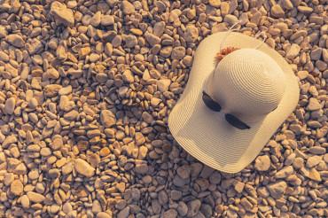 Sun Hat and Sunglasses on a Rocky Beach