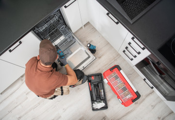 Technician Installing Dishwasher Inside Residential Apartment Kitchen