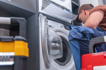 Technician Repairs Broken Washing Machine