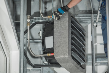 Technician Servicing Warehouse Heating Unit Attached to Building Wall
