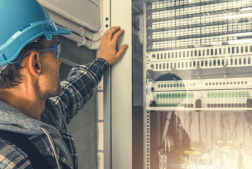 Telecommunication Technician Looking Inside Servers Rack