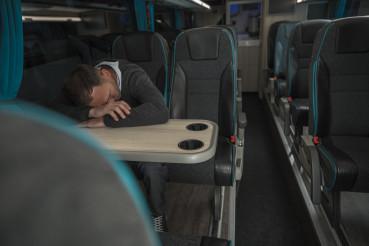Tired Businessman Sleeping on Coach Bus Table