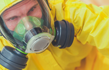 Tired Caucasian Worker in Hazmat Suit and Face Mask