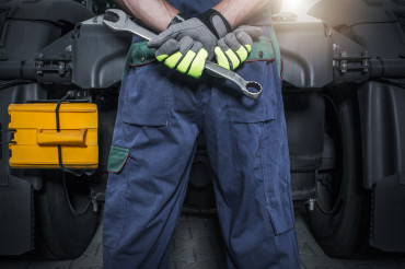 Truck Mechanic in Front of Tractor with Wrench in His Hands