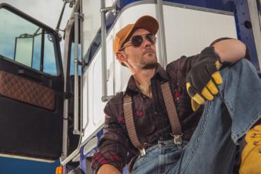 Trucker Relaxing Next to His Semi Truck