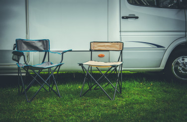 Two Empty Camping Deckchairs in Front of RV Camper