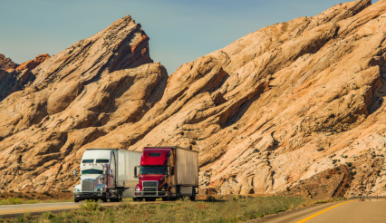 Two Semi Trucks Passing Scenic Utah Landscape