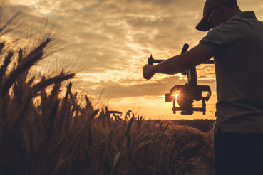 Video Camera Operator with Gimbal Stabilization Taking Scenic Sunset Shot
