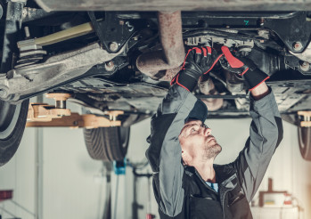 Mechanic Fixing Car Hoisted Up On Hydraulic Lift.