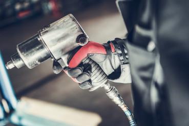 Mechanic Holding Pneumatic Wrench Gun.