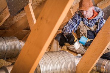 Male Contractor Binding Ventilation Pipes With Duct Tape.