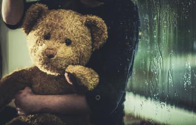Child With Teddy Bear Sitting On Windowsill At Night.