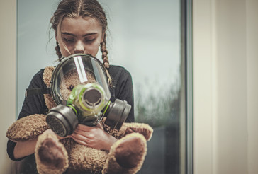 Girl Holding And Protecting Teddy Bear With Gas Mask.