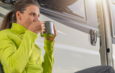 Woman Drinking Cup of Hot Coffee in Front of Her Camper Van