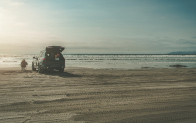 Woman Enjoying Beach Place Seating Alone Next to Her Car