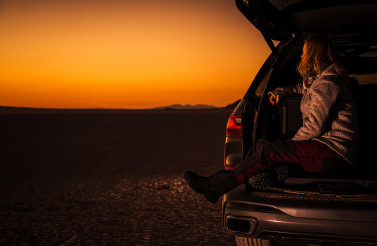 Woman Enjoying Scenic Sunset From Her Car