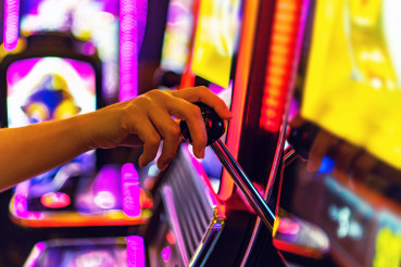 Woman Playing One Handed Casino Slot Game