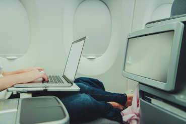 Woman Remotely Working While in Airplane Business Class
