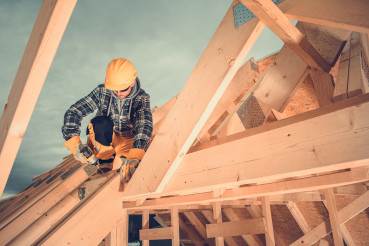 Wooden House Roof Beams Assembly by Construction Worker