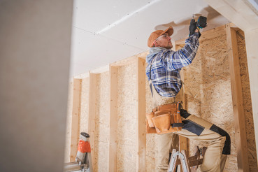Worker Attaching Drywall