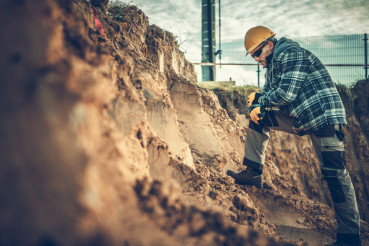 Worker Checking on a Soil