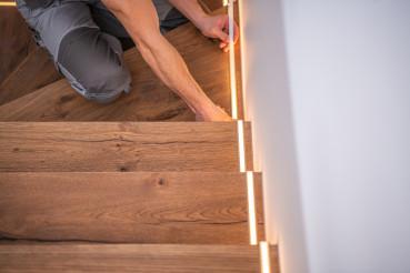 Worker Finishing LED Stairs Illumination Installation