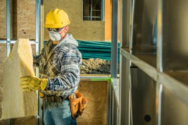 Worker in Safe Breathing Mask Working Inside Developed Building
