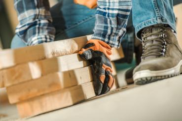 Worker Moving Wood Beams Close Up