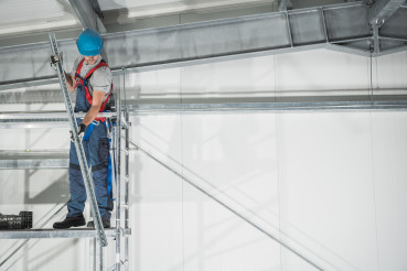 Worker on Scaffolding Finishing Warehouse Building