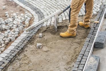 Worker Paving Residential Path Using Granite Bricks