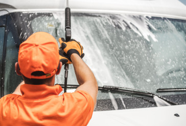 Worker Pressure Washing Commercial Vehicle