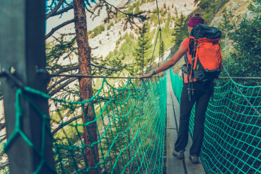 Female Hiker Crossing Small Suspension Bridge.