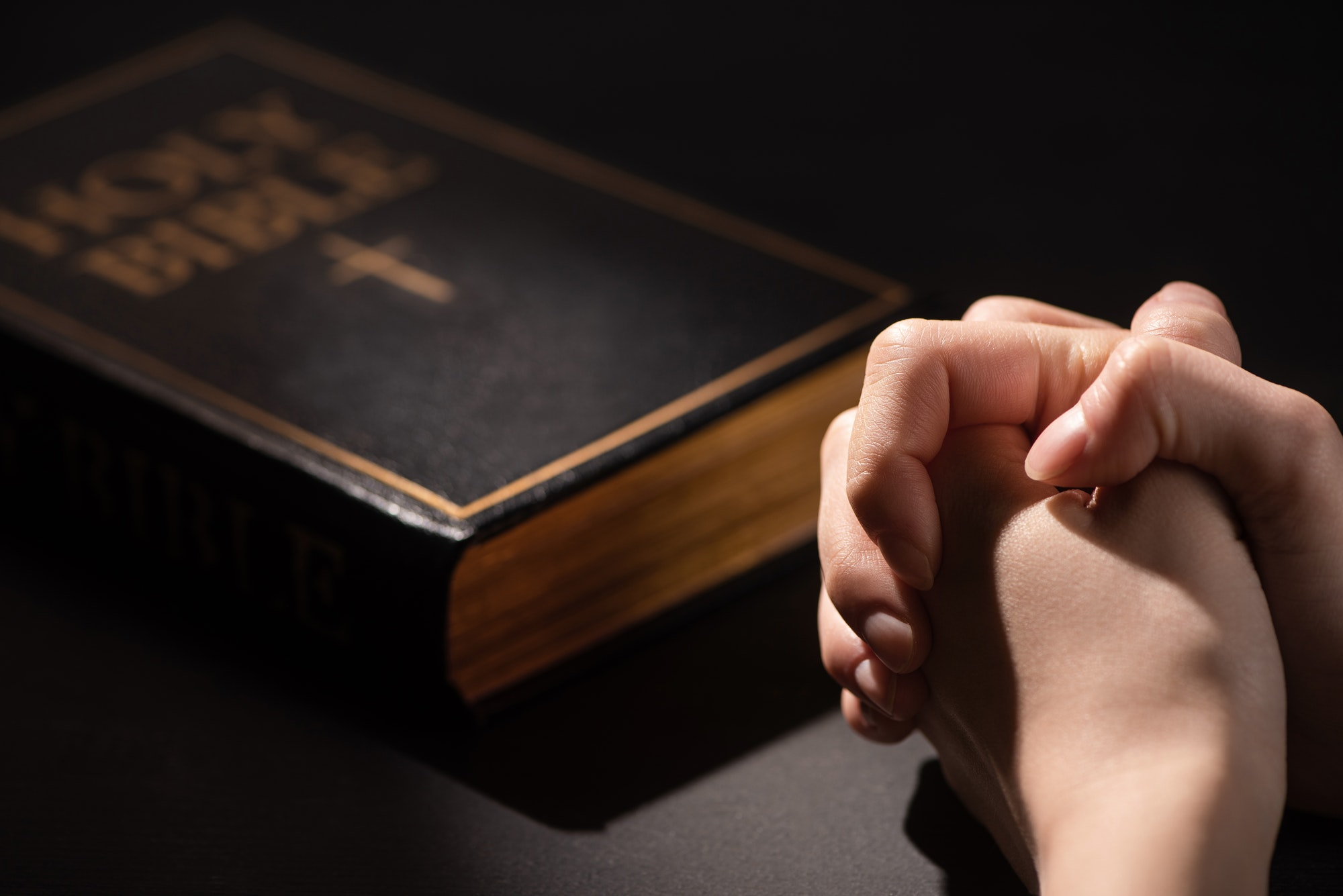 Cropped View of Woman Praying Near Holy Bible in Dark
