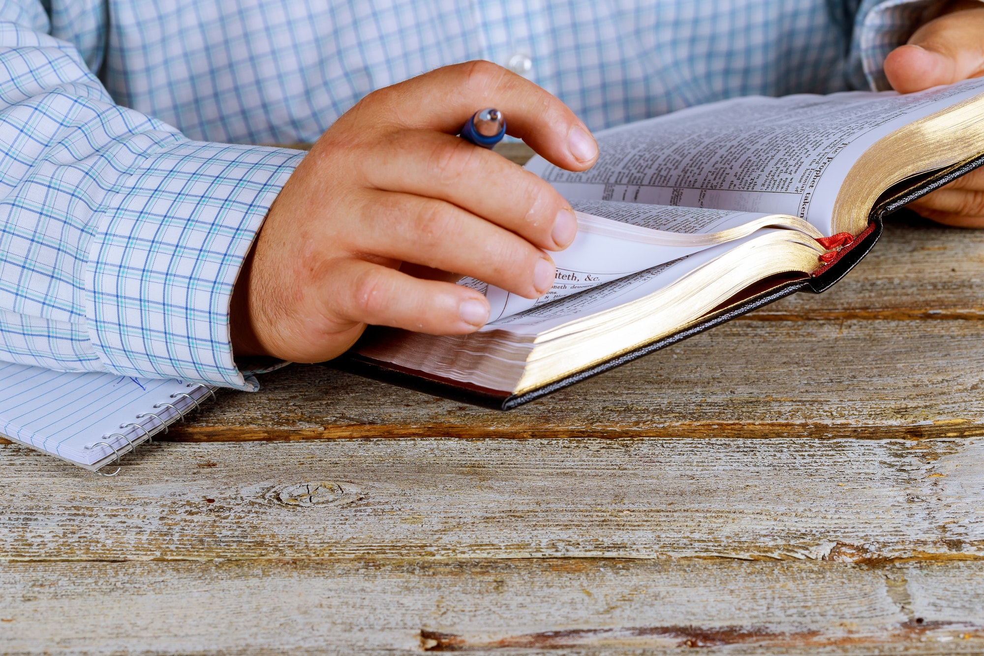 Man is holding a pen in his hand with an open book Holy Bible lying in fornt of him